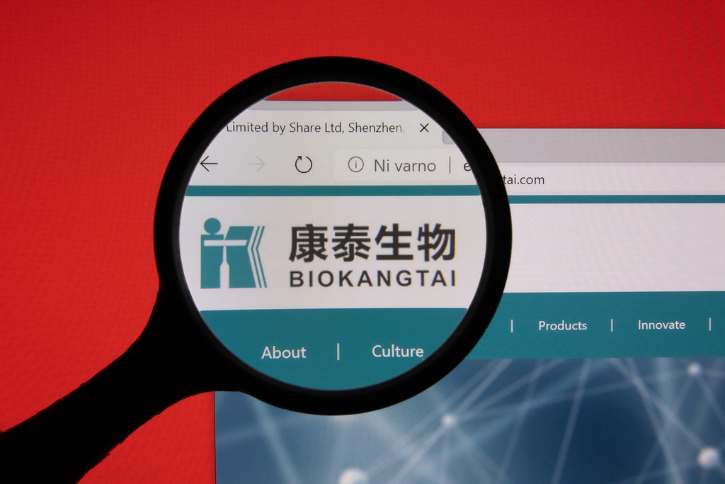 Bio Kangtai website page logo on laptop display with red background