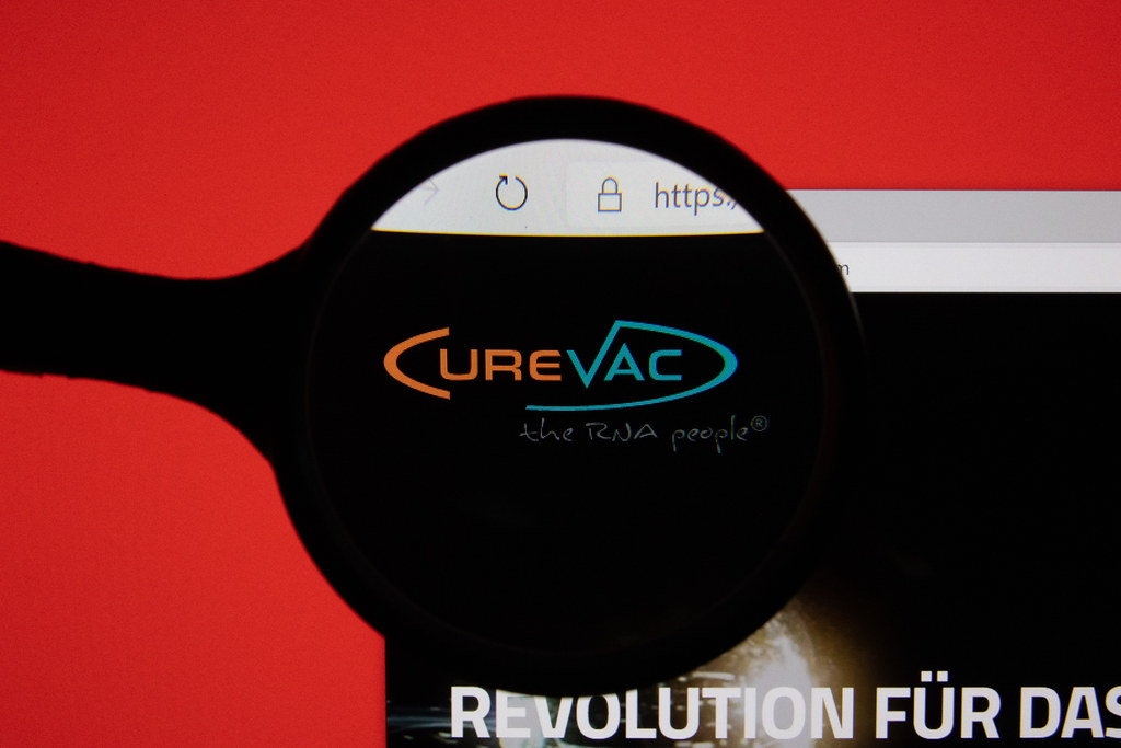 CureVac website page logo on laptop display with red background