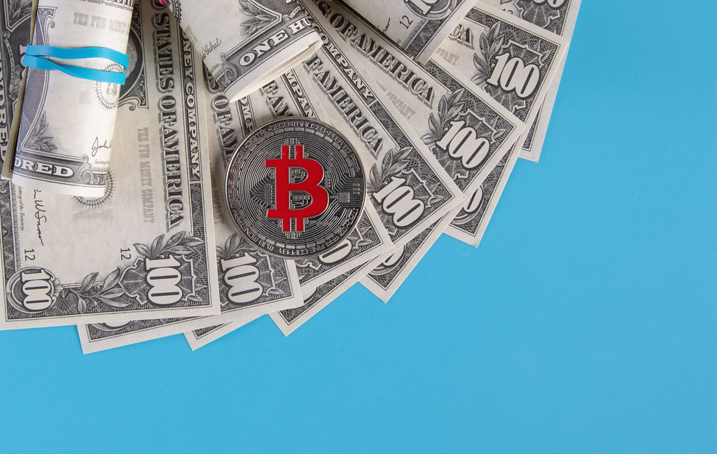 A symbolic coins of bitcoin on banknotes of one hundred dollars.